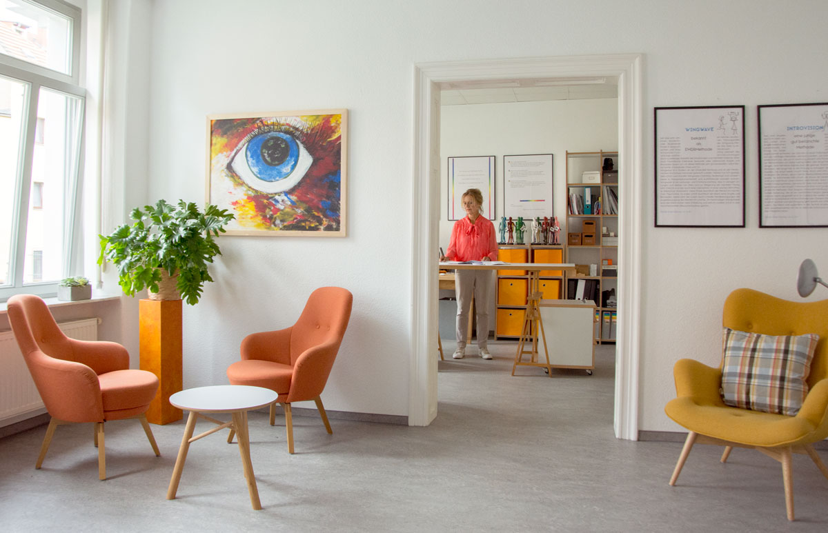 Blick vom Seminarraum ins Bürozimmer. Frau Baudis steht in Ihrem hellen Büro hinter dem holzenden Tisch. Sie trägt bunte korallfarbene Bluse und helle Leinenhose. Im Hintergrund sind die mehrfarbigen Modellpuppen aus Holz zu sehen.