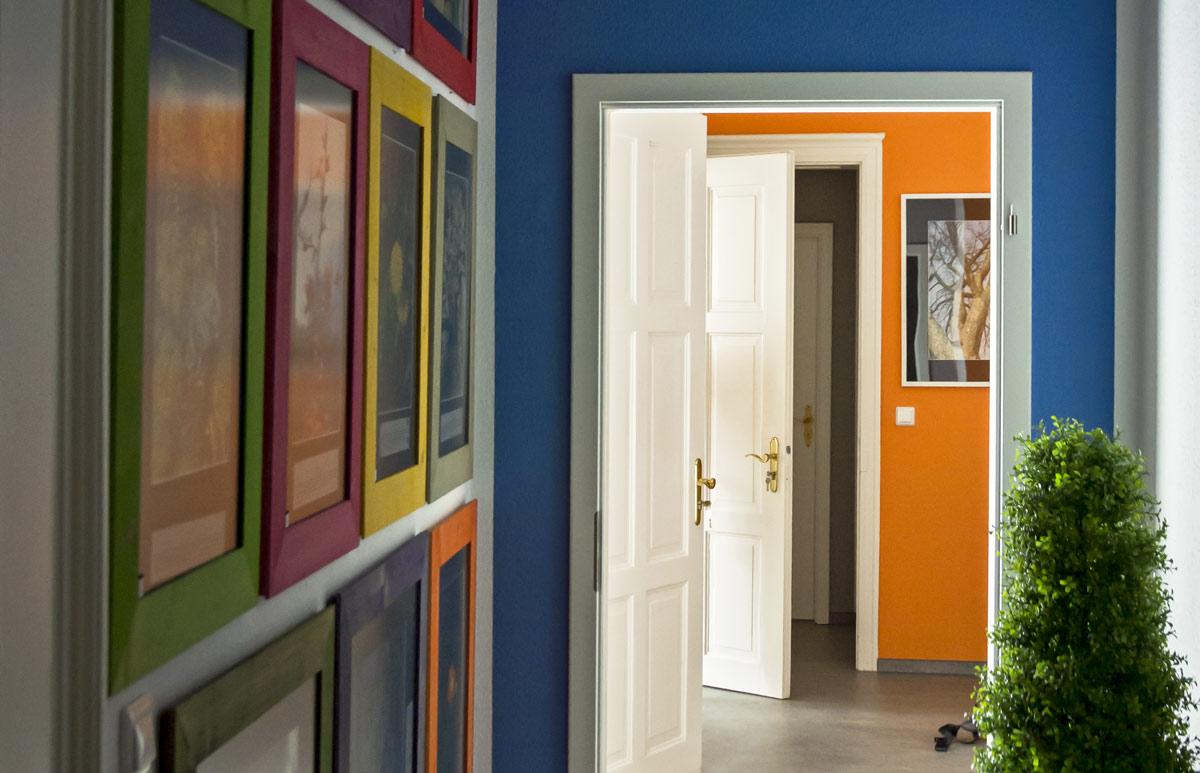 Der Blick vom Korridor in die Büroräume. An den Wänden sind viele Bilder in bunten Rahmen zu sehen. Die Wände vom Korridor sind blau bestrichen, die Wände des gegenüberliegenden Zimmers sind bunt orange bestrichen. Im linken Winkel des Bildes ist eine grüne Pflanze zu sehen.