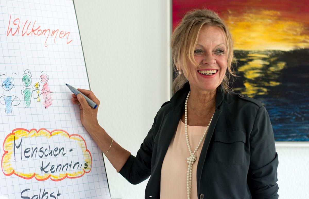 """Elka Baudis steht vor einer Konferenz-Staffelei. Auf dem sind bunte Menschen gezeichnet, die Wörter """"Willkommen"""" und """"Menschen-Kenntnis"""". Im Hintergrund ist ein Bild mit dem Sonnenuntergang zu sehen. Frau Baudis lächelt und zeigt mit dem Filzstift auf die Tafel. Sie trägt einen dunklen Blazer-Jacke und helle Bluse."""