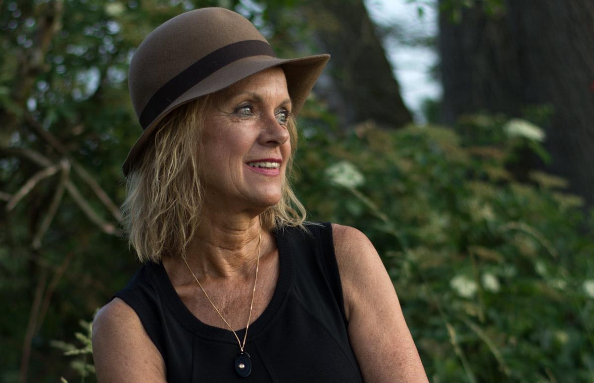 Nahaufnahme von Elka Baudis in der Natur im Abendlicht untergehender Sonne. Sie schaut nach rechts, lächelt, Ihre Haare sind offen, sie trägt ein Hut und eine schwarze ärmellose Bluse. Im Hintergrund sind Bäume zu sehen.